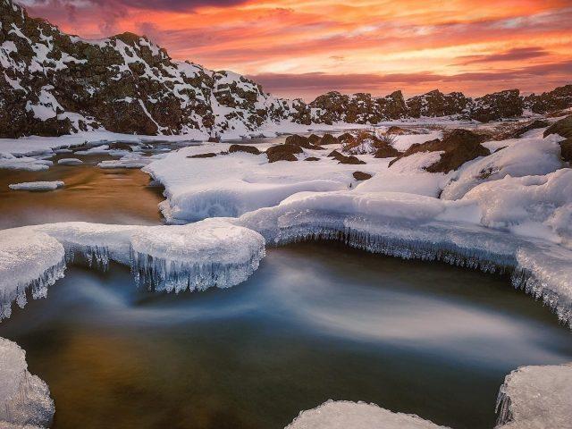 Исландская река со снегом во время заката в зимней природе