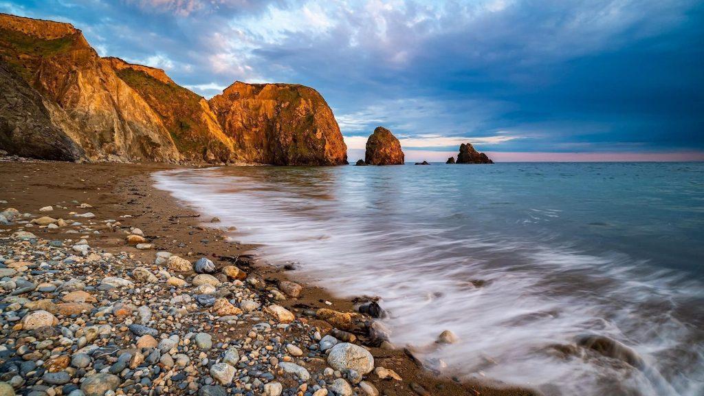 Скалы на волнах морские камни под голубым облачным небом природа обои скачать