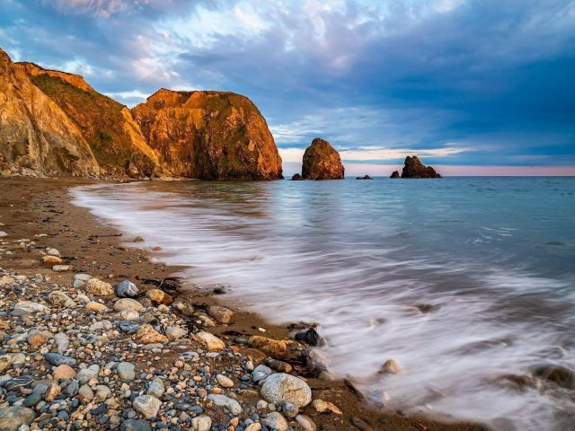 Скалы на волнах морские камни под голубым облачным небом природа