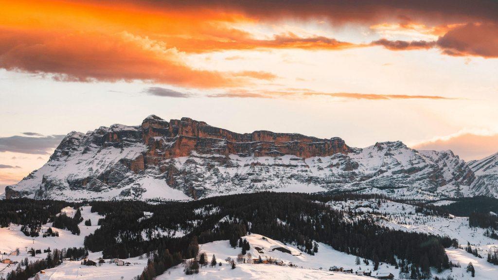 Прекрасный вид на горы покрытые снегом и деревьями покрытый лес под черно желтым облачным небом природа обои скачать