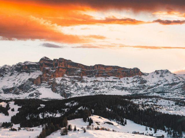 Прекрасный вид на горы покрытые снегом и деревьями покрытый лес под черно желтым облачным небом природа