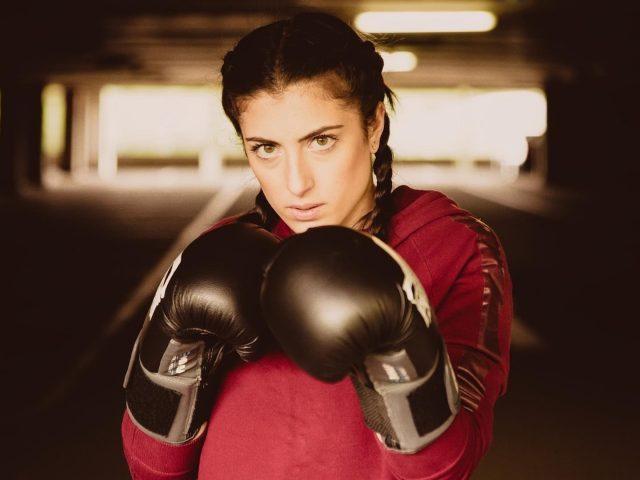 Коса карие глаза с черными боксерскими перчатками одета в красное платье бокс