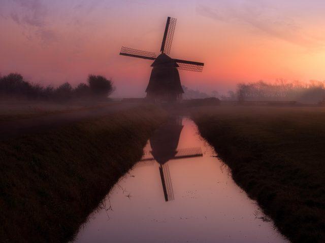 Ветряная мельница nederland во время заката с отражением на водоеме природы