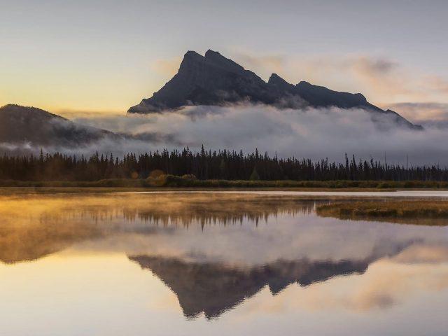 Снегом между деревьями, с горы отражение в озере