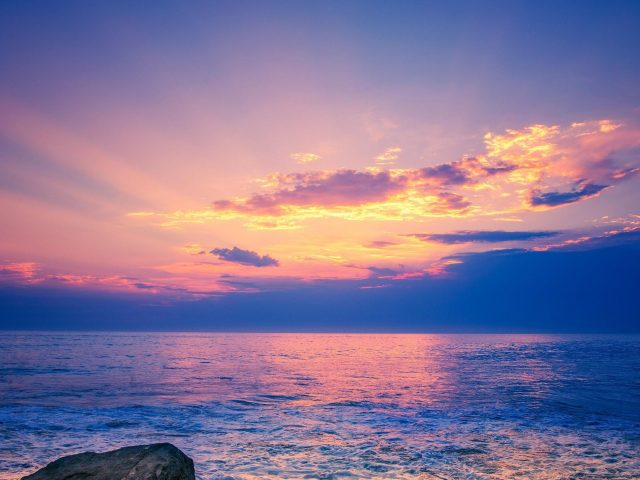 Светло-фиолетовое небо над пляжной скалой природа