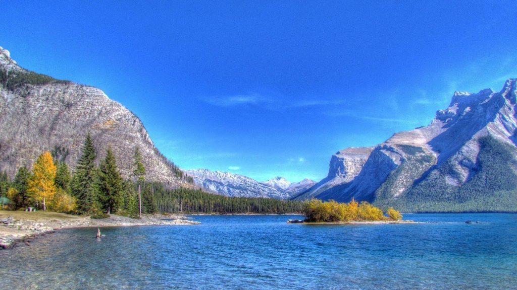 Пляж река в окружении каменных гор под голубым небом природа обои скачать
