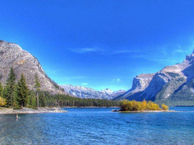 Пляж река в окружении каменных гор под голубым небом природа