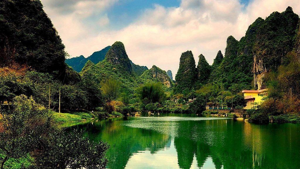 Пейзажный вид на покрытые зелеными растениями горы с отражением речной природы обои скачать