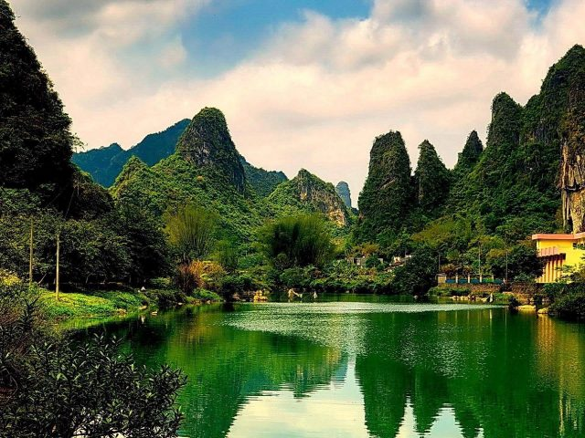 Пейзажный вид на покрытые зелеными растениями горы с отражением речной природы