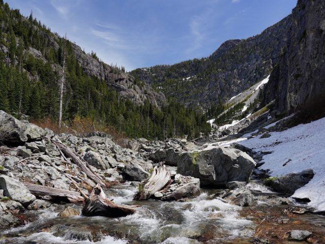 Река камни скалы деревья лес горы снег под голубым небом природа