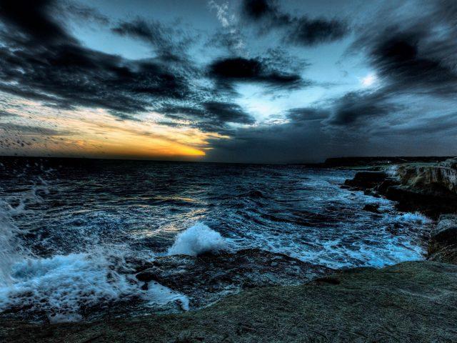 Темные облака под бурным морем с коричневыми скалами во время заката природа