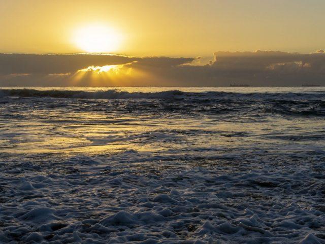 Океанские волны в черно-желтых облаках на фоне неба во время заката природа