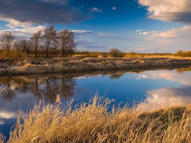 Сухое поле между рекой с отражением облаков в дневное время природа