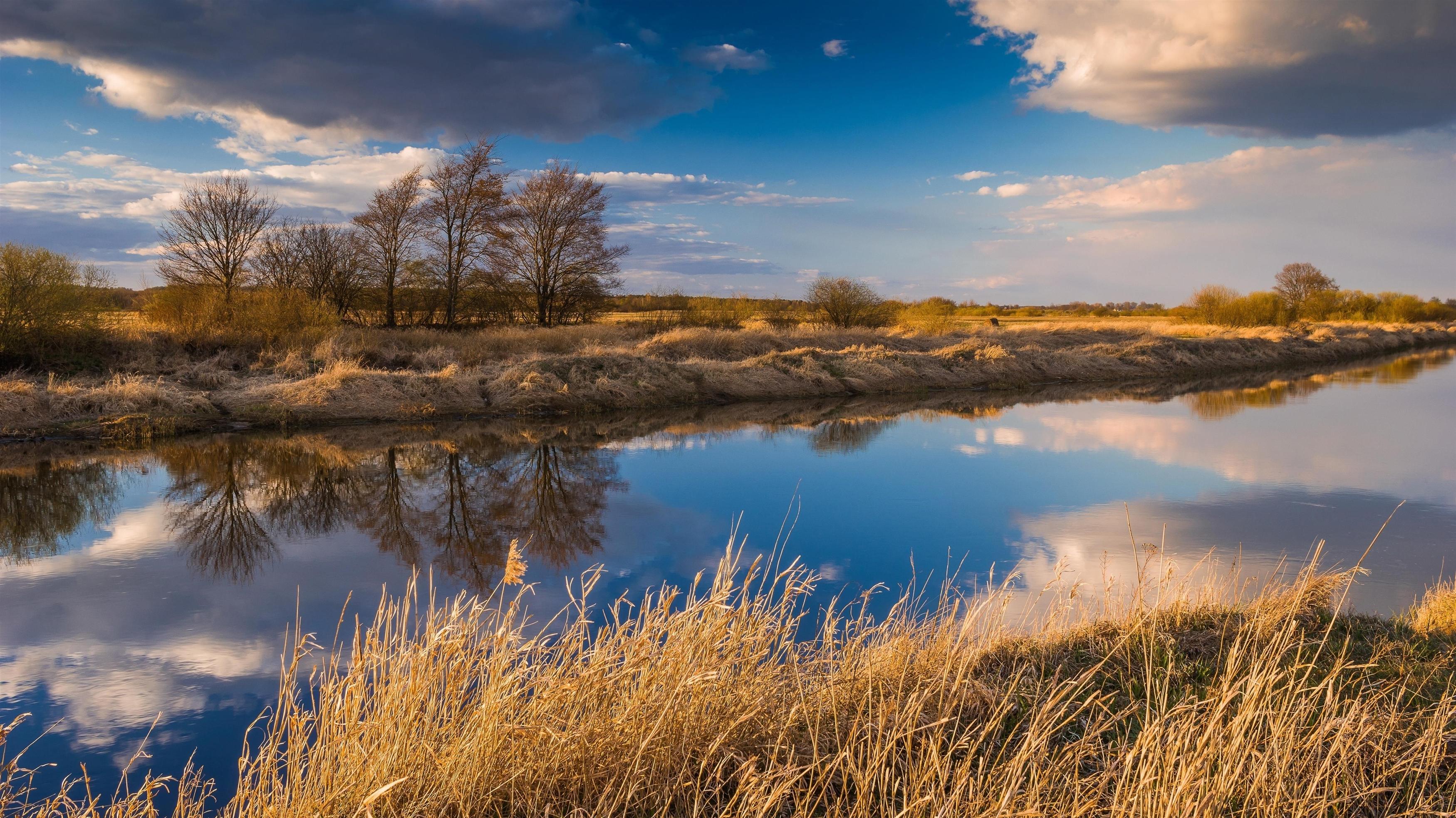 Сухое поле между рекой с отражением облаков в дневное время природа обои скачать