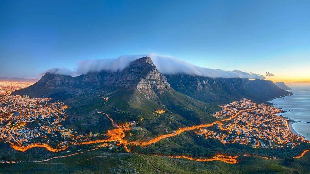 Пейзаж вид на покрытую туманом гору в окружении освещения дороги и зданий природа обои скачать