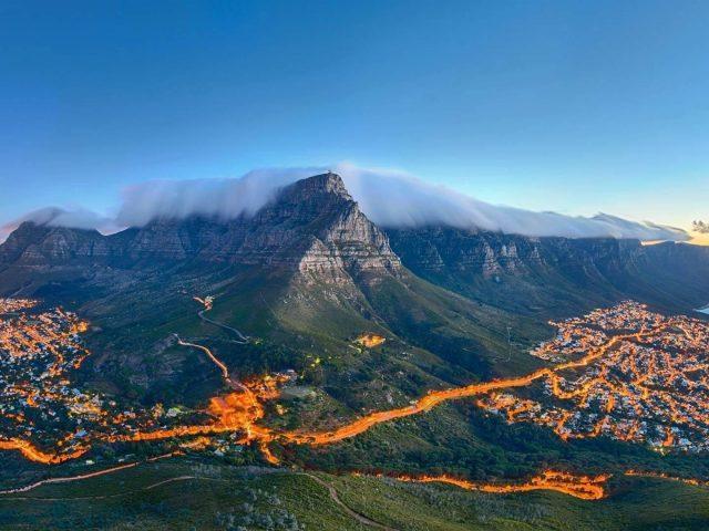 Пейзаж вид на покрытую туманом гору в окружении освещения дороги и зданий природа