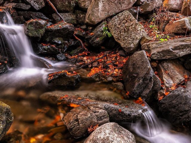 Водопады между валунами и речной природой
