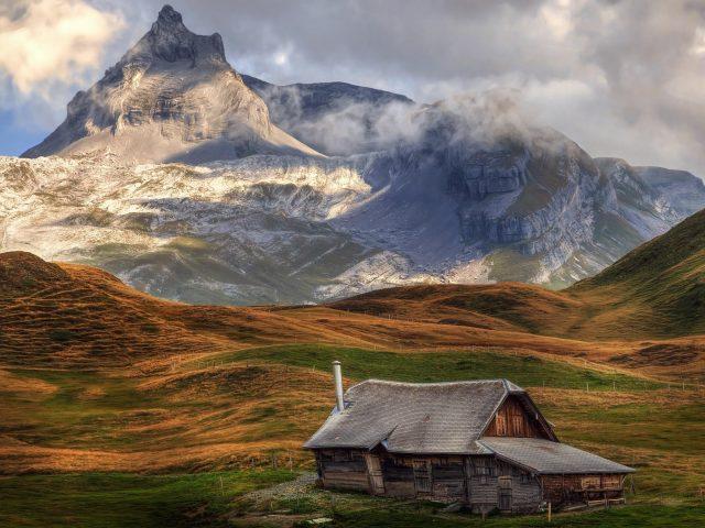 Заснеженная гора с зеленой покрытой горой и искусственной хижиной природа