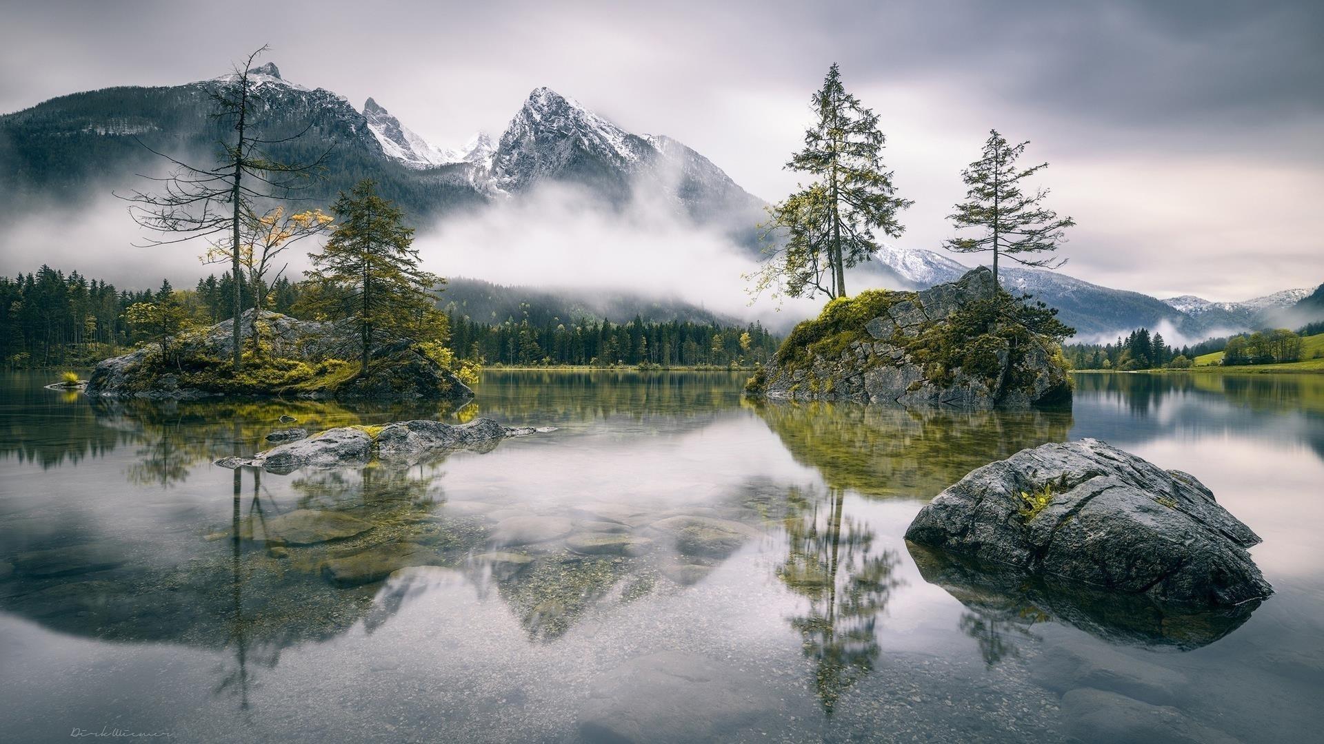 Заснеженная гора с туманом и покрытая зеленью скала с деревьями в водной природе обои скачать