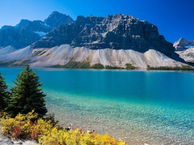 Пейзажный вид на горы под голубым небом и спокойный водоем в дневное время природа