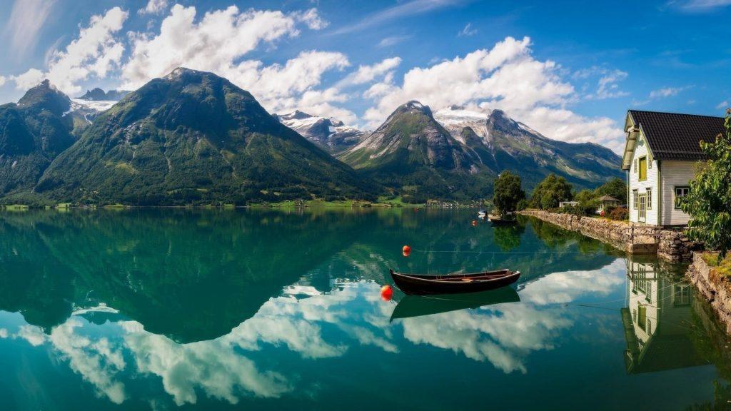 Лодка на реке с отражением гор и бело голубого облачного неба природа обои скачать