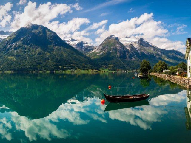 Лодка на реке с отражением гор и бело голубого облачного неба природа